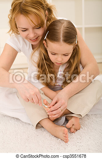 Personal grooming - woman and little girl cutting toe nails - csp3551678