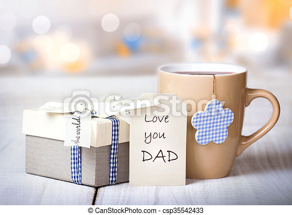 Father\'s day holiday greeting card.Mug tea coffee and present gift box tag on wooden table blur lights background empty space.Love you dad message.