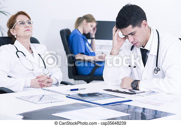 Tired group of medics sitting in light hospital office