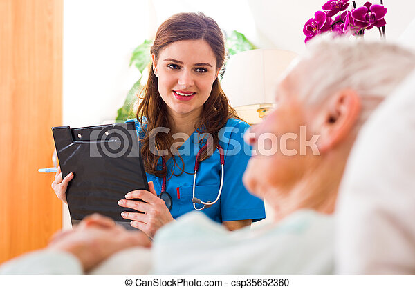 Kind nurse with clopboard in her hands registering senior woman\'s healthcare stats.