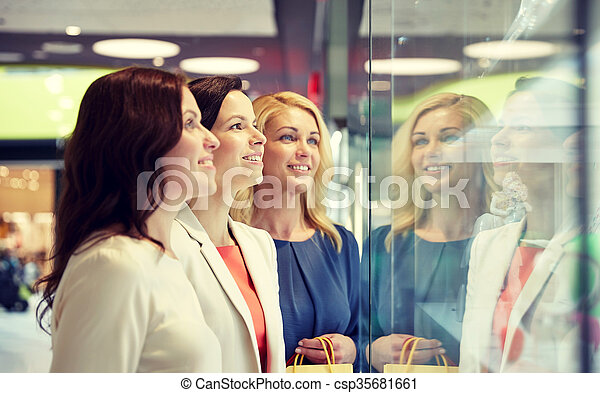 sale, consumerism, shopping and people concept - happy women looking at jewelry shop window in mall