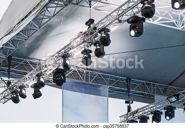 lighting equipment with spotlights under roof of outdoor stage during the rain