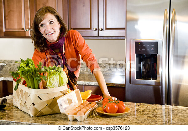 Mature woman in kitchen with fresh produce - csp3576123