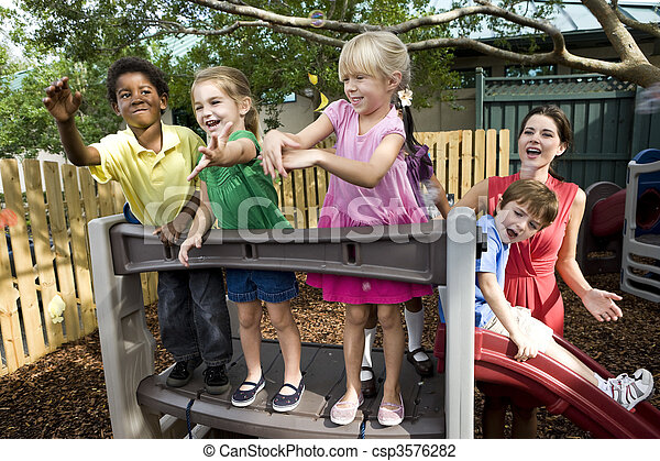 Preschool children playing on playground with teacher - csp3576282