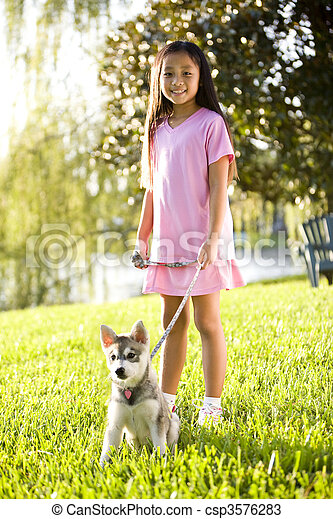 Young Asian girl walking puppy on leash on grass - csp3576283