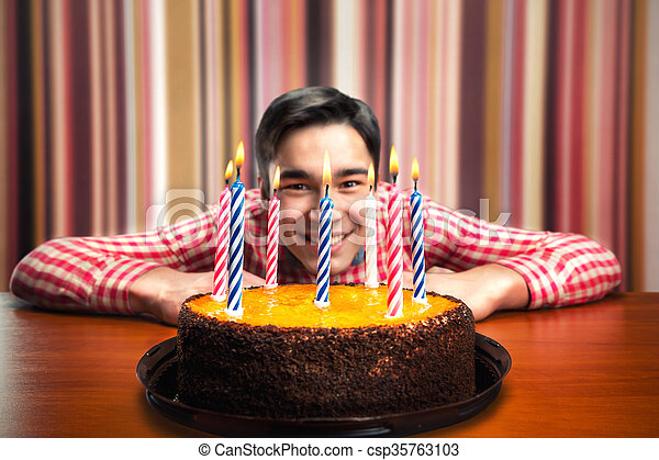 Happy birthday boy with cake with candles in decorated room