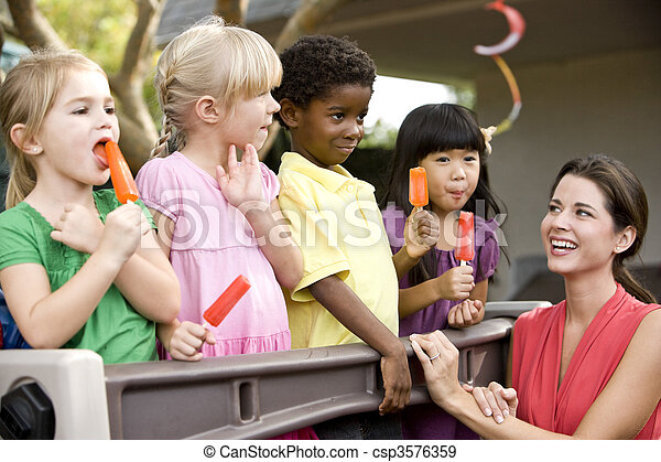 Diverse group of preschool 5 year old children playing in daycare with teacher - csp3576359
