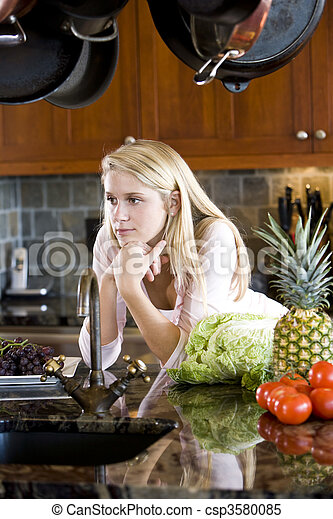Teenage girl leaning on kitchen counter thinking - csp3580085