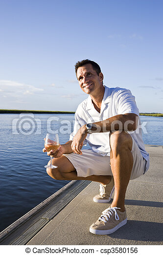 Mid-adult man on dock by water enjoying drink - csp3580156