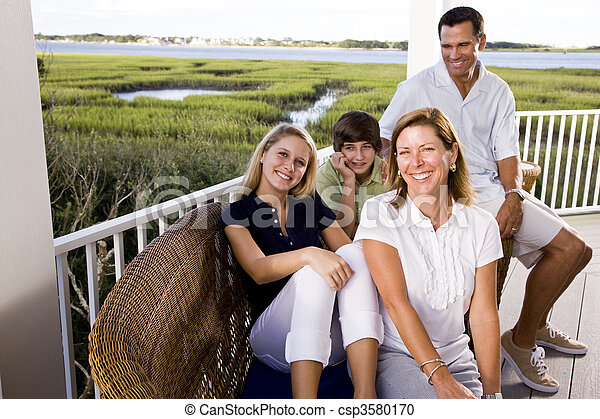 Family on vacation sitting together on terrace - csp3580170