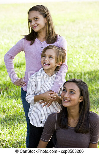 Three close siblings together outdoors on sunny day - csp3583286