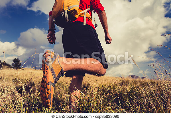 Hiking man or trail runner walking in mountain inspirational landscape. Fitness and healthy lifestyle hiker or trekker walk on dry grass, fall autumn nature. Travel in Italy, Europe. Selective focus on a sports shoe.