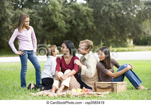 Affectionate modern multicultural family enjoying a picnic - csp3583419