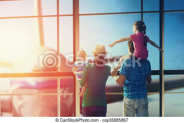Happy family with children at the airport. Parents and their children look out the window at the plane.