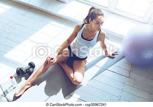 Relaxing after training. Top view of beautiful young woman looking away while sitting on exercise mat at gym