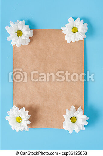 Kraft envelope and white chrysanthemums on a blue background. Romantic letter and message. Copy space and room for the signature. Spring mood.