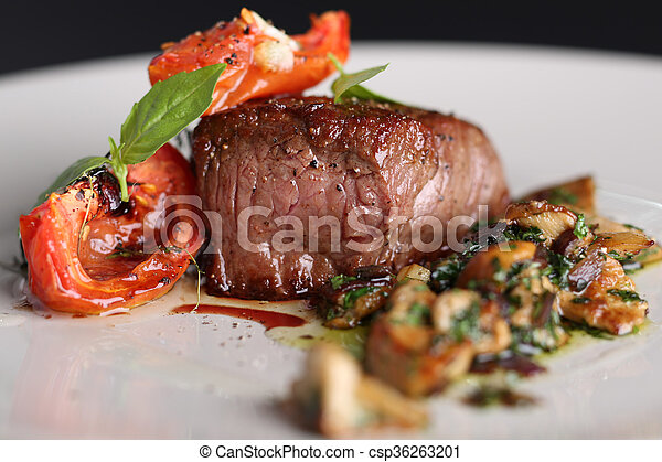 Roasted meat with tomatoes and mushrooms on a white plate, dark background in the restaurant. Close up