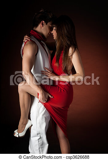 Young couple dancing embrace passion romance on dark red light background. - csp3626688