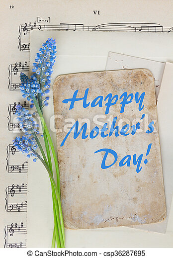 Muscari blue flowers and aged paper note with happy mothers day greeting card
