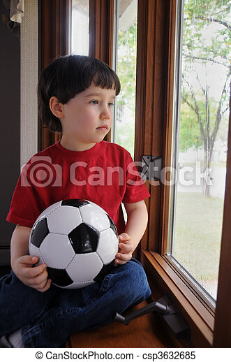 Boy wants to play soccer on a rainy day - csp3632685