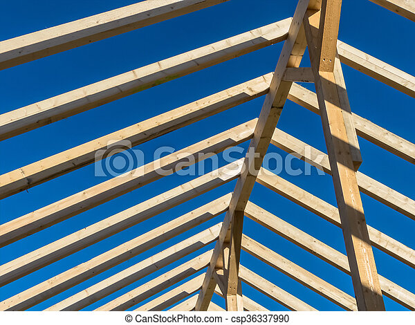in a house with a new roof is being built on a construction site. carrier wooden roof truss.