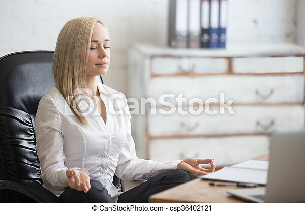 Business and healthy lifestyle concept. Portrait of young office woman sitting cross-legged in easy yoga pose at workplace. Smiling business lady meditating on her break time