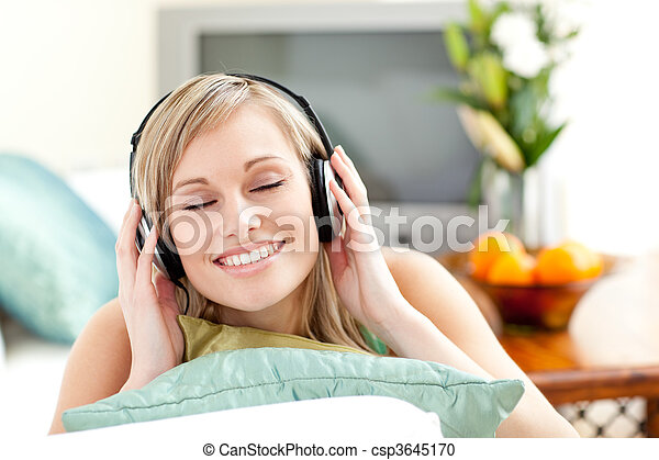 Delighted young woman listening music lying on a sofa  - csp3645170