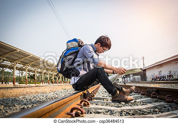 Traveler wearing backpack holding map on railway at train station, vintage tone. travel concept.