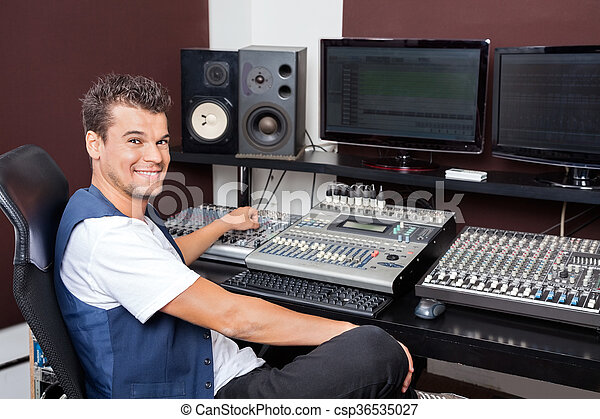 Portrait Of Young Man Mixing Audio In Recording Studio - csp36535027