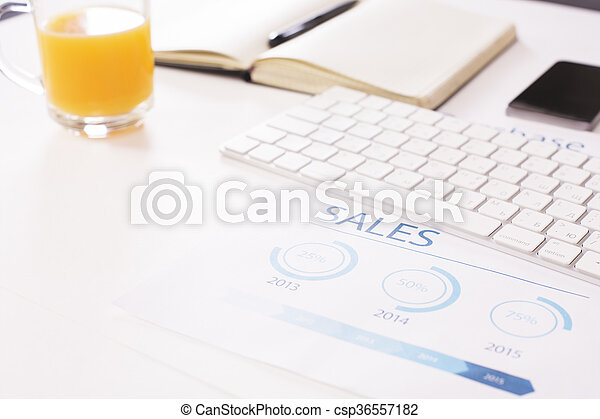 Closeup of white office desk with business report, orange juice, keyboard and other items