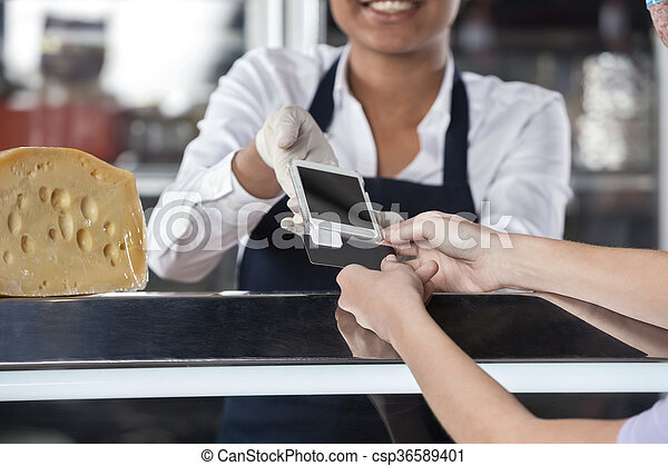 Woman Making Payment Through Credit Card At Cheese Shop - csp36589401