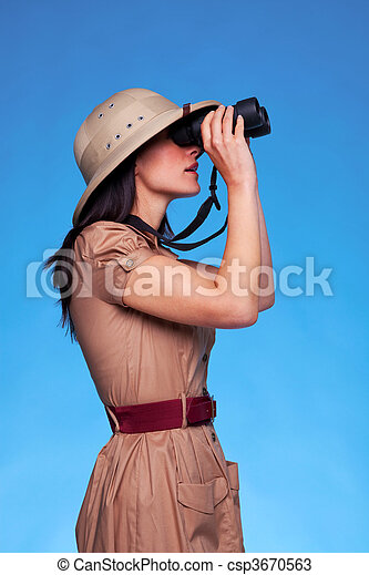 Woman in safari hat looking through binoculars side view - csp3670563