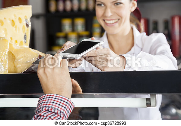 Saleswoman Accepting Payment From Customer Through Credit Card - csp36728993
