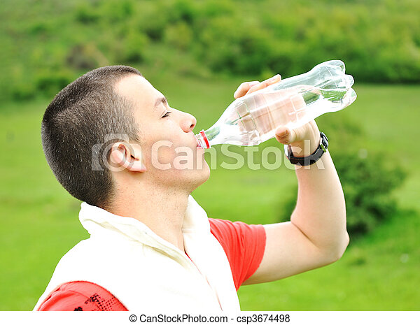 Young man drinking water in nature