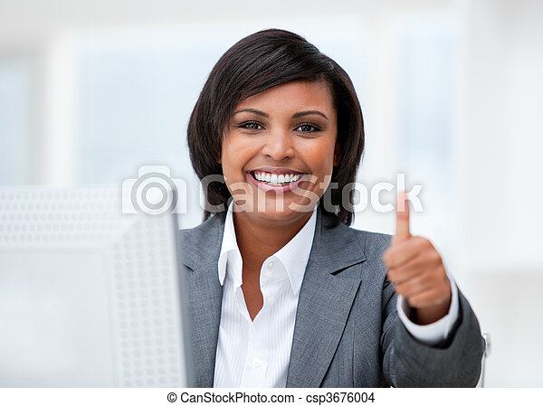 Happy businesswoman with a thumb up working at a computer - csp3676004