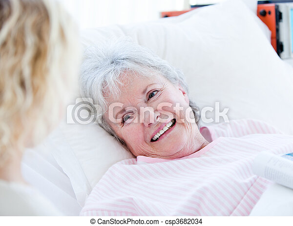 Smiling senior woman lying on a hospital bed talking with her granddaughter. Medical concept. - csp3682034