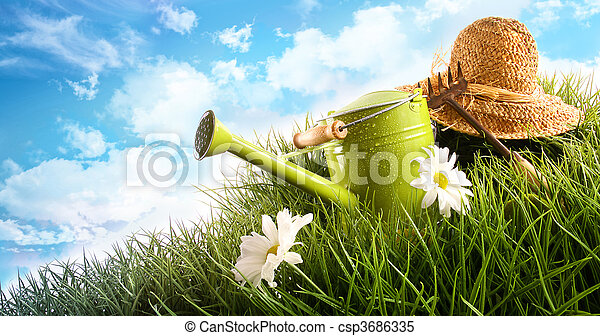 Water can and straw hat laying in grass - csp3686335