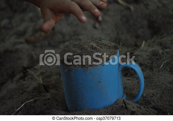 Sand, mug, child\'s play in the sand. Hands of the child.