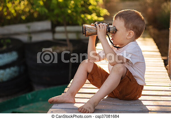 Portrait of little boy looking through binoculars on river bank. Barefoot child with binoculars sitting on the pier on river