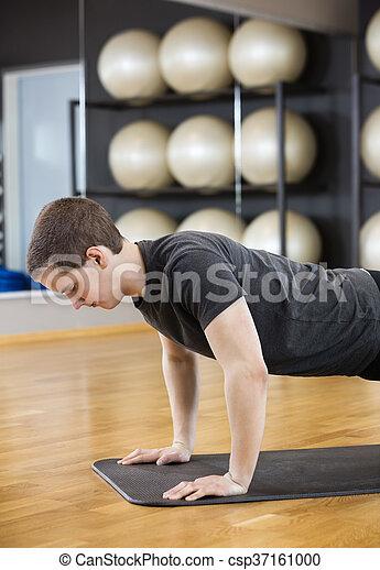 Man Performing Pushups On Mat In Gym - csp37161000