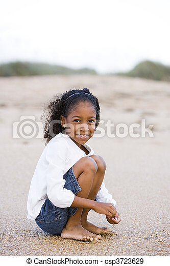 Cute six year old African-American girl on sand at beach - csp3723629