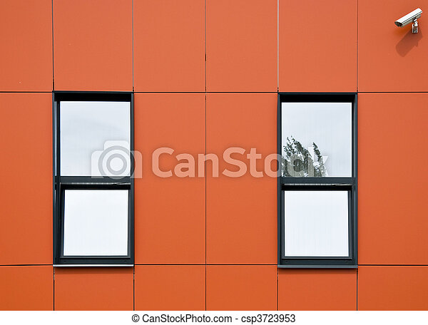 Orange facade of aluminum panels. Two windows and surveillance cameras, which looks onto the street. Close-up. Fragment. - csp3723953