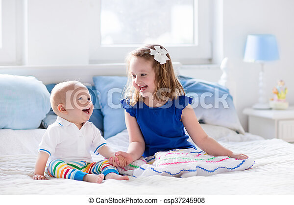 Little girl and baby boy, brother and sister playing in parents bed. Family with children in the morning. Kids play in white bedroom. Nursery crib bedding and textile for young child. Siblings love.