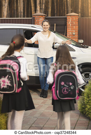 Two cheerful girls running to mother meeting them after school