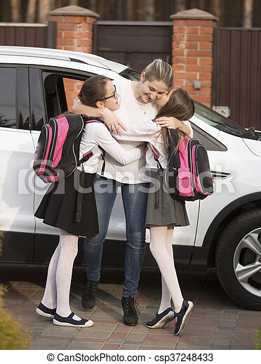 Happy mother meeting daughters near the car after lessons in school