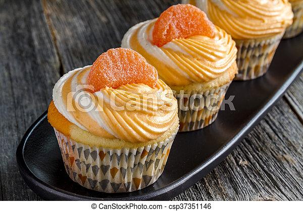 Stock Photo of Orange Vanilla Bean Swirled Cupcakes - Row of orange ...
