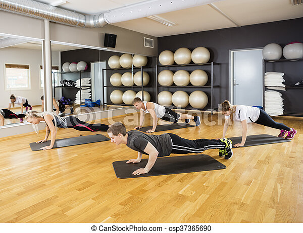 Friends Performing Plank Exercise In Gym - csp37365690