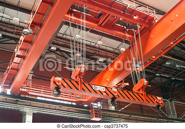 Large-tonnage industrial orange Goliath crane loading of goods in factory mill - csp3737475