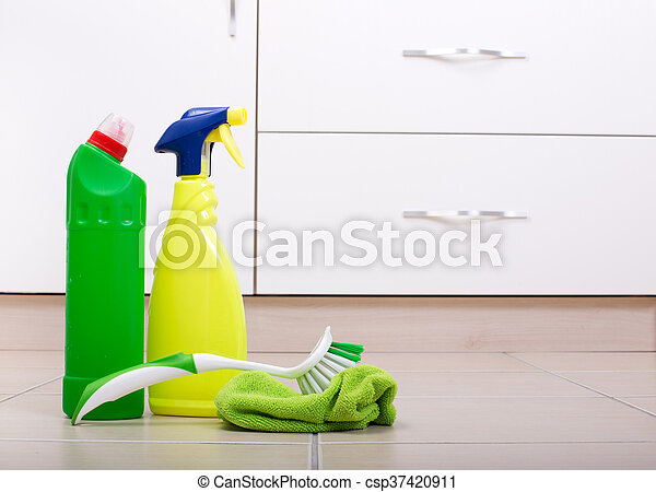 Close up of two bottles of cleaning detergent with cloth and brush on kitchen floor and kitchen cabinets in background