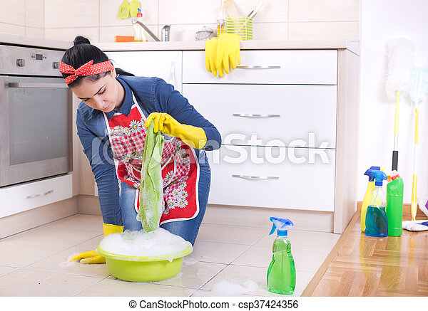 Young pretty woman cleaning kitchen floor with cloth and foam from basin